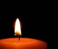 Röd stearinljusbränning med den blåa flamman Svart bakgrund fotografering för bildbyråer