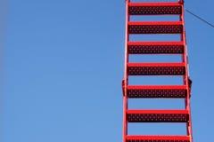 Röd stege från metall mot den blåa himlen, generös kopieringsspac royaltyfri bild
