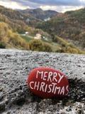 Röd sten för glad jul med landskapbakgrund Royaltyfria Foton