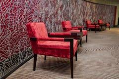 Röd stol för lyxig tappning som isoleras på röd bakgrund arkivbild