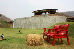 Röd stol i lantgård Arkivfoto