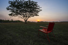 Röd stol i solnedgång och lutninghimmel Royaltyfria Foton