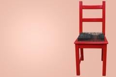 Röd stol med grova spikar på platsen Royaltyfri Foto