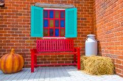 Röd stol med tegelstenväggen Arkivbild