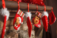 Röd strumpa för jul som hänger från en spiselkrans eller en spis, dekor royaltyfri fotografi
