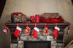 Röd strumpa för jul som hänger från en spiselkrans eller en spis, dekor royaltyfria foton