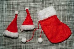 Röd strumpa för julgarnering och jultomtenhatt på grått bakgrundsslut upp arkivbilder