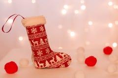 Röd strumpa med hjortar för handgjorda gåvaställningar mot bakgrunden av julljus och mjuka bollar royaltyfri fotografi