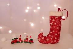 Röd strumpa med hjortar för handgjorda gåvaställningar mot bakgrunden av julljus, stearinljus och mjuka bollar royaltyfri foto