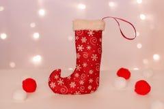 Röd strumpa med snöflingor för handgjorda gåvaställningar på bakgrunden av julljus och mjuka bollar royaltyfri fotografi