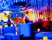 Röd tärning i coctailexponeringsglaset framme av vardagsrumstångkasinot Royaltyfri Bild
