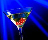 Röd tärning i coctailexponeringsglaset på blått ljust kasinobegrepp Royaltyfria Bilder