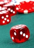 Röd tärning på en kasinotabell med chiper Royaltyfri Bild