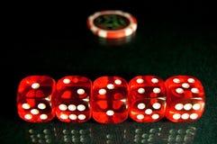Röd tärning på pokertabellen Arkivfoton