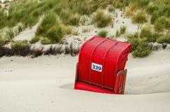 Röd taklagd vide- strandstol på den Helgoland dyn, Schleswig-Holstein, Tyskland royaltyfri foto