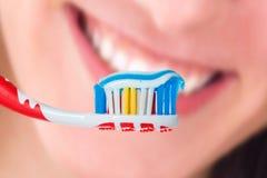 Röd tandborste med färgtandkräm för blått två på mänskligt leende Arkivbilder