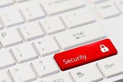 Röd tangent med textsäkerhet och stängd hänglåssymbol på det vita bärbar datortangentbordet Royaltyfri Bild