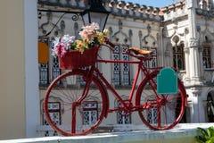Röd tappningcykel med färgrika blommor i korgen Royaltyfri Bild