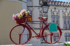 Röd tappningcykel med färgrika blommor i korgen Arkivfoton
