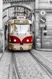 Röd tappningspårvagn i de gamla gatorna av Prague Fotografering för Bildbyråer