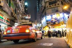 Röd taxitaxi nära Nathan Road i Hong Kong Fotografering för Bildbyråer