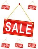 Röd teckenetikett med inskriftförsäljningen som hänger på en repvecto Arkivfoto