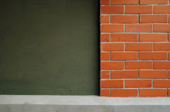 Röd tegelsten och mörk vägg för gräsplan i Lanscape Royaltyfri Bild