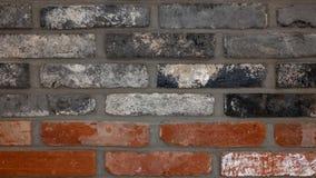 Röd tegelsten, svart tegelsten, grov textur arkivbilder