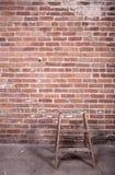 Röd tegelstenvägg och stege Arkivfoto