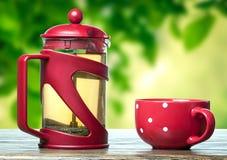Röd tekanna och kopp med te Arkivfoton