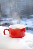 Röd tekopp i insnöad jul för morgonvinterlynne Arkivfoton