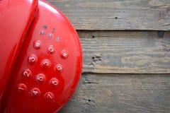 Röd telefon på trätabellen Royaltyfri Fotografi