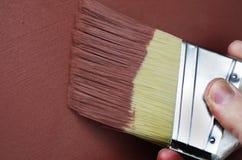 Röd texturerad målarfärg som appliceras med borsten Arkivbilder