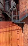 Röd timmervägg med svart järntrappa arkivbilder