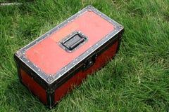 Röd tin boxas på en grön lawn arkivbilder