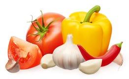 Röd tomat, gul klocka och chilipeppar, vitlök med kryddnejlikor Arkivfoton