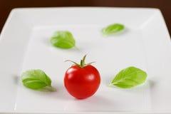 Röd tomat med basilikasidor på den vita plattan arkivbild