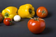 Röd tomat på en mörk bakgrund Röd tomat på en bakgrund av olika grönsaker Royaltyfria Foton