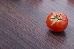 Röd tomat på en träbrun tabell Ny röd närbild för körsbärsröd tomat på en tabell Royaltyfria Foton