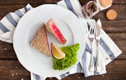 Röd tonfiskbiff med citronen på wood bakgrund arkivfoton