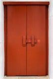 Röd trädörr med det traditionella låset för arg stång Royaltyfri Bild