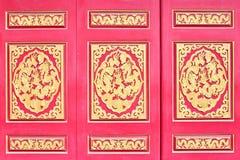 Röd trädörr med kinesiska guld- drakar Arkivbild