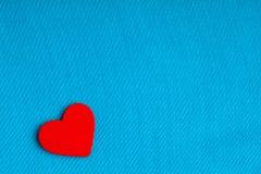 Röd trädekorativ hjärta på blå torkdukebakgrund. Royaltyfria Foton