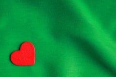 Röd trädekorativ hjärta på gräsplan viker bakgrund. Arkivbild