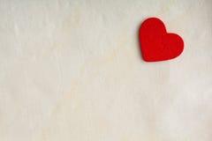 Röd trädekorativ hjärta på vit torkdukebakgrund. Arkivbilder