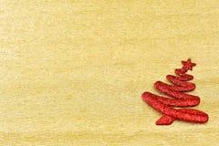 Röd trädgarnering för jul på guld- bakgrund Arkivbild
