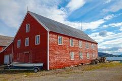 Röd träfiska ladugård med det lilla fartyget Royaltyfri Foto