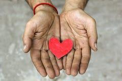 Röd trähjärta i smutsiga händer royaltyfri foto