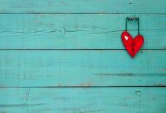Röd trähjärta som hänger på turkosbakgrund Arkivbilder