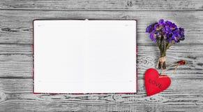 Röd trähjärtahänge, en öppen dagbok med rengöringsidor och torkade blommor Romantiskt begrepp Bakgrunder och texturer Arkivfoto